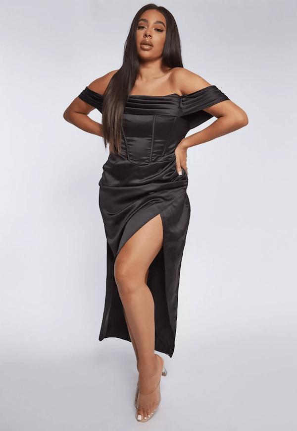 A model wearing a plus-size black maxi dress.