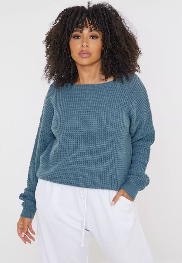 A model wearing a plus-size off-the-shoulder sweater in dusty teal.
