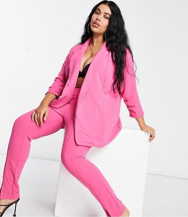A model wearing a plus-size pant suit in pink.