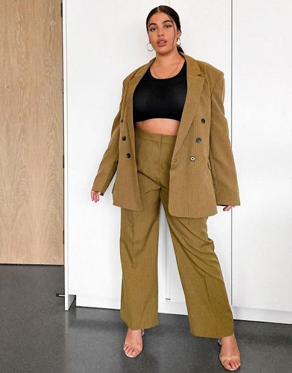 A model wearing a plus-size pant suit in olive green.