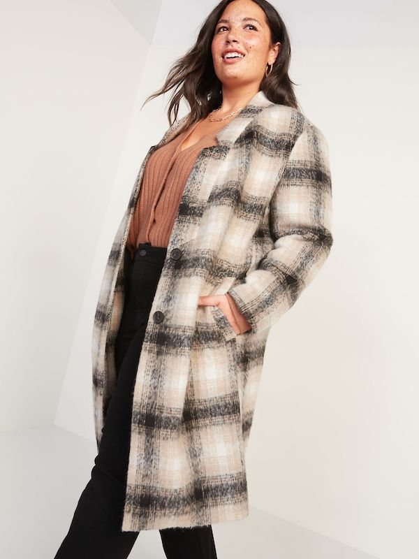 A model wearing a plus-size plaid coat in cream and brown.