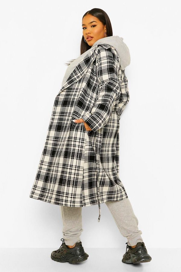 A model wearing a plus-size plaid coat in black and white.