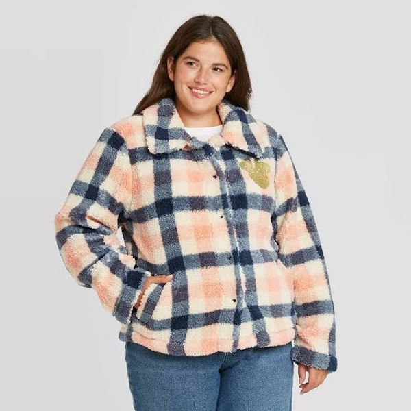 A model wearing a plus-size plaid coat in orange and navy.