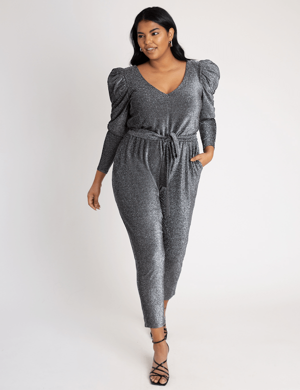 A model wearing a plus-size silver jumpsuit.