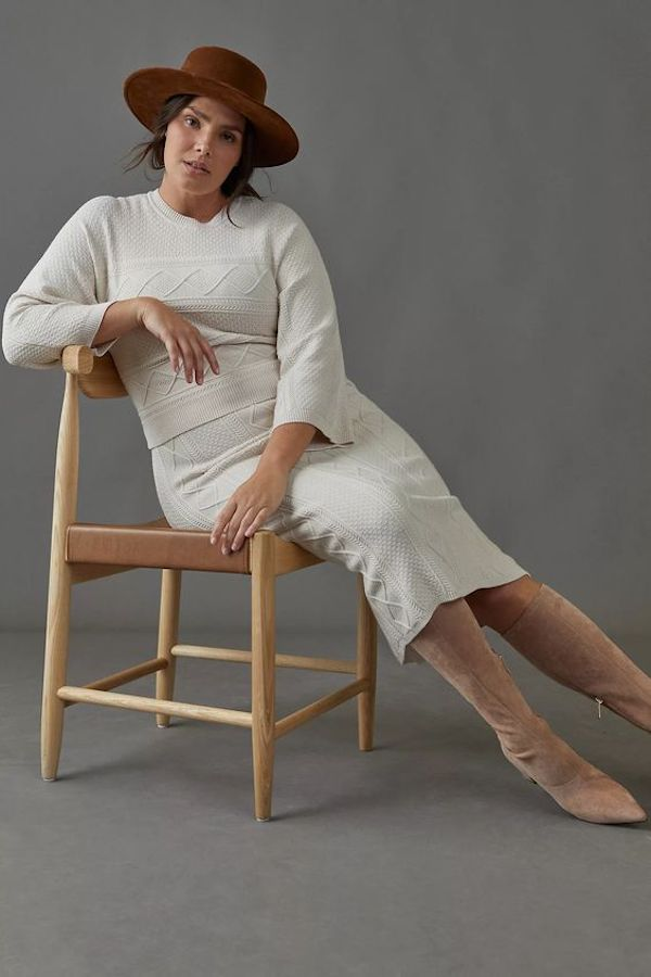 A model wearing a plus-size cream sweater dress.