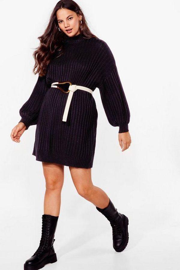 A model wearing a plus-size turtleneck dress in black.