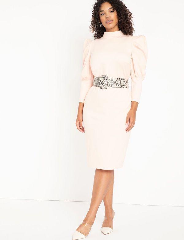 A model wearing a plus-size turtleneck dress in light pink.