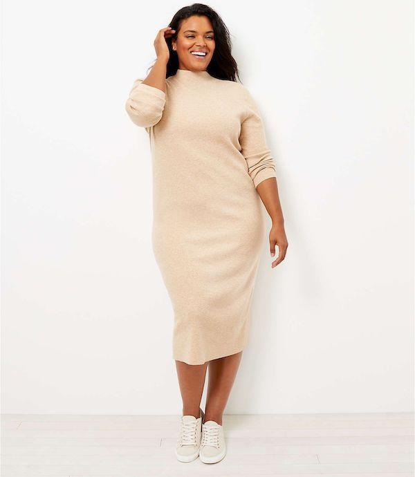 A model wearing a plus-size turtleneck dress in cream.