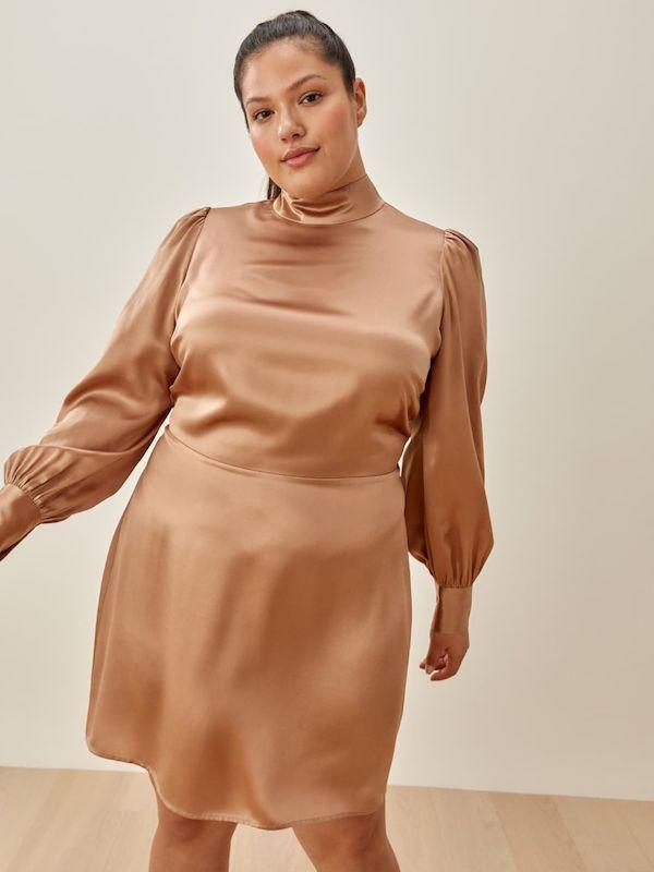 A model wearing a plus-size turtleneck dress in silky gold.