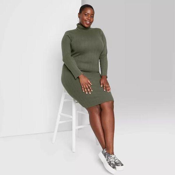 A model wearing a plus-size turtleneck dress in dark green.
