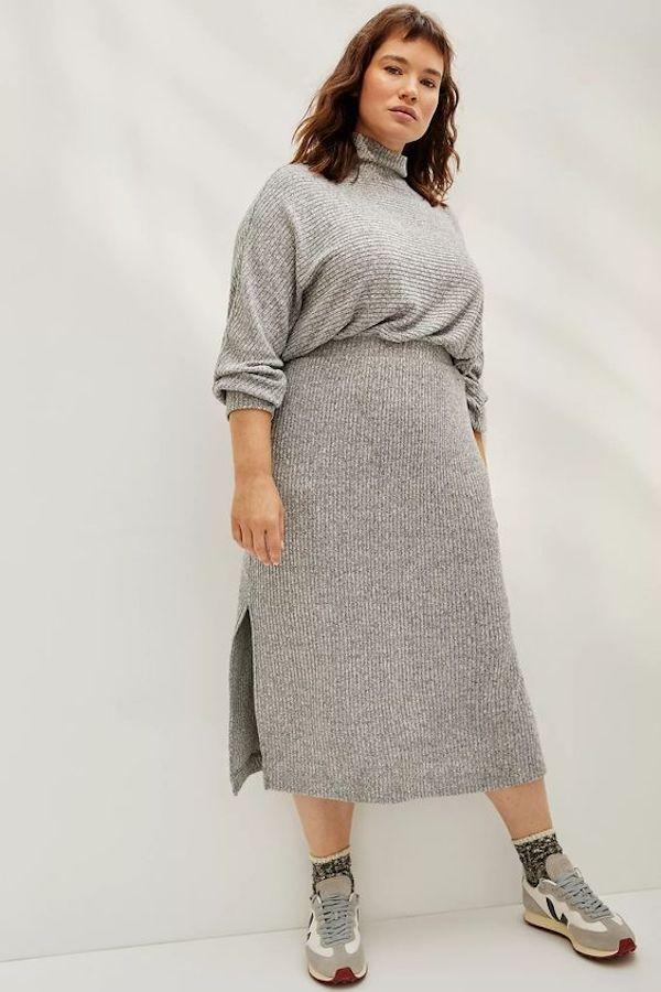 A model wearing a plus-size turtleneck dress in gray.