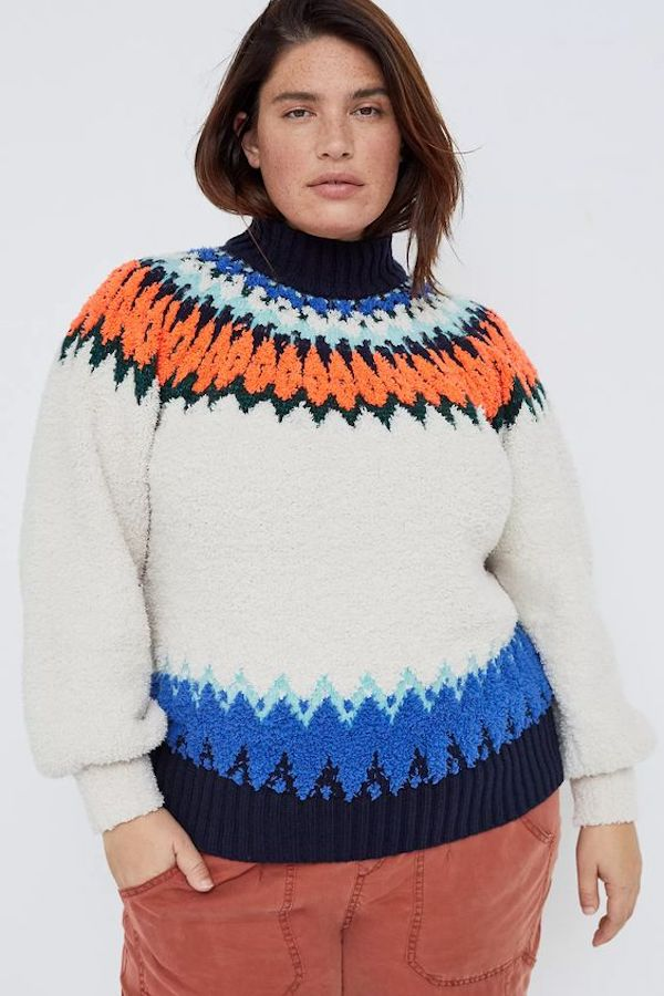 A model wearing a plus-size turtleneck sweater in white with blue and orange fairisle.