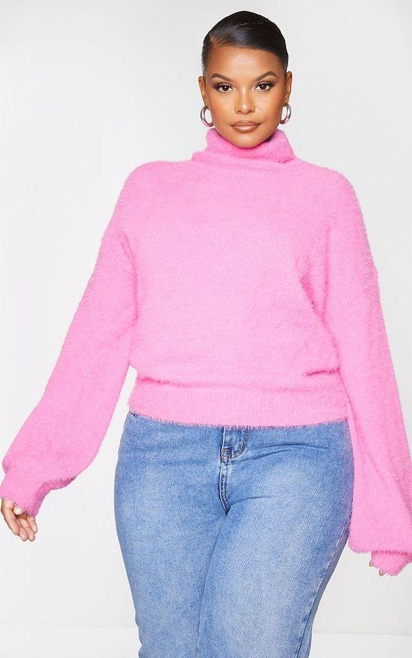 A model wearing a plus-size turtleneck sweater in pink.