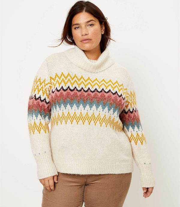 A model wearing a plus-size turtleneck sweater in cream with yellow, red, and green fairisle.