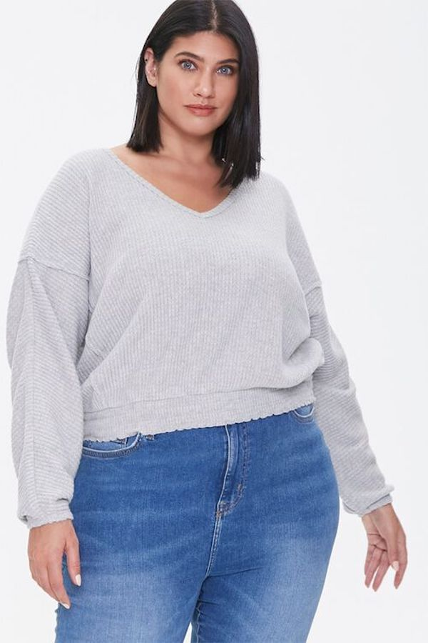 A model wearing a plus-size v-neck sweater in gray.