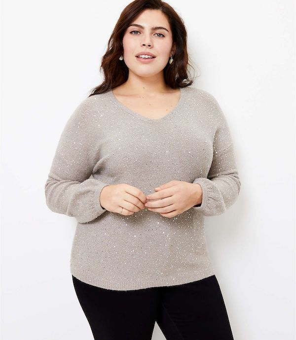 A model wearing a plus-size v-neck sweater in taupe.