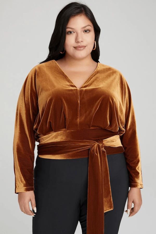 A model wearing a plus-size dark gold velvet top.