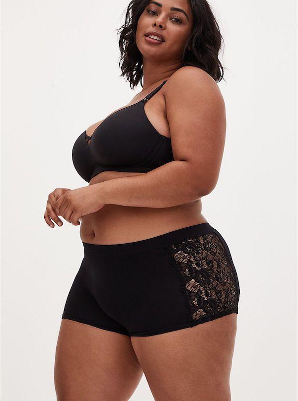 A model wearing plus-size boyshorts in black.