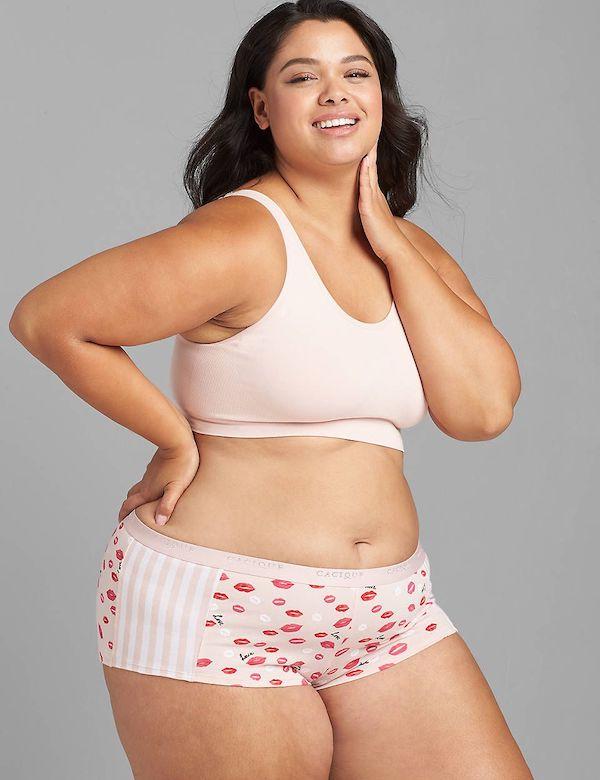 A model wearing plus-size boyshorts in pink heart pattern.