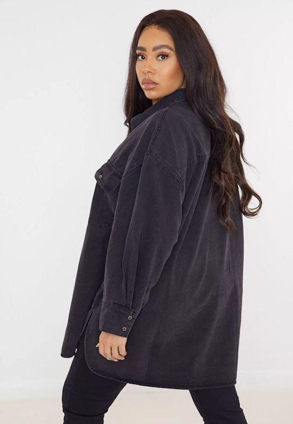 A model wearing a plus-size denim shirt in black.