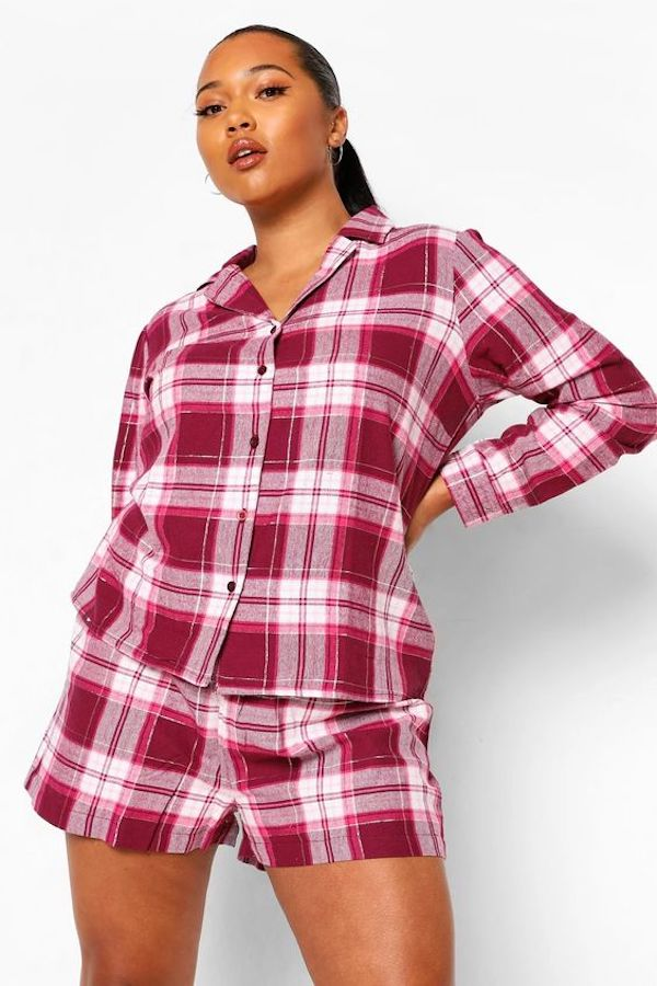 A model wearing plus-size flannel pajamas in pink and red plaid.