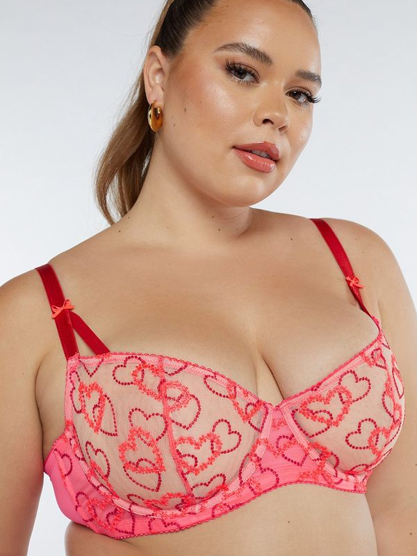 A model wearing a plus-size lace pink bra with hearts.