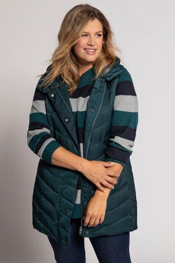 A model wearing a plus-size puffer vest in dark teal.