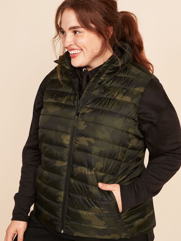 A model wearing a plus-size puffer vest in camo.