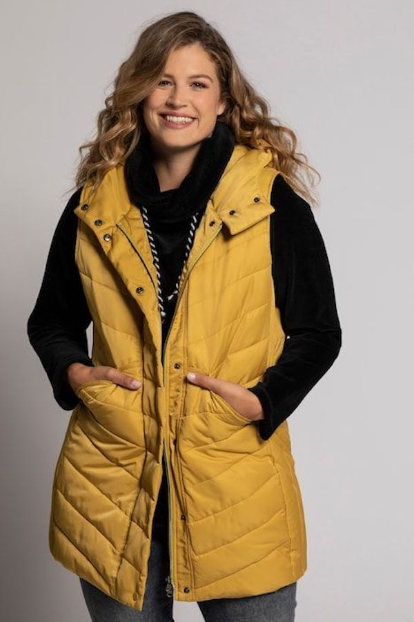 A model wearing a plus-size puffer vest in mustard.