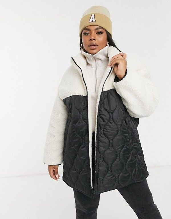 A model wearing a plus-size quilted jacket in black and white.