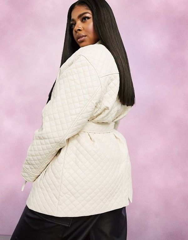 A model wearing a plus-size quilted jacket in cream.