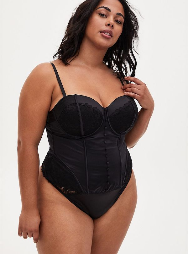 A model wearing a satin black lingerie bodysuit.