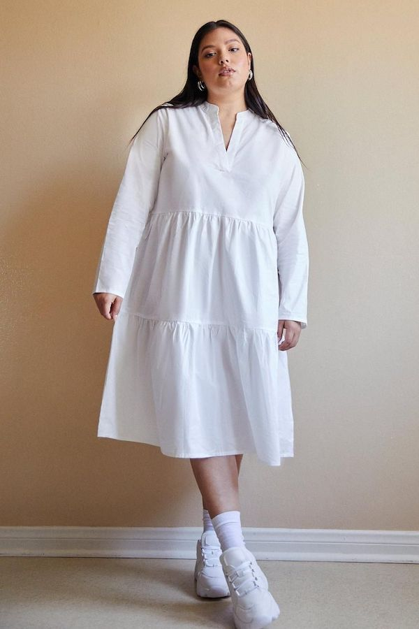 A model wearing a plus-size smock dress in white.