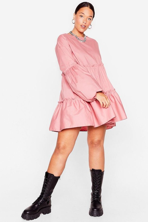 A model wearing a plus-size smock dress in pink.