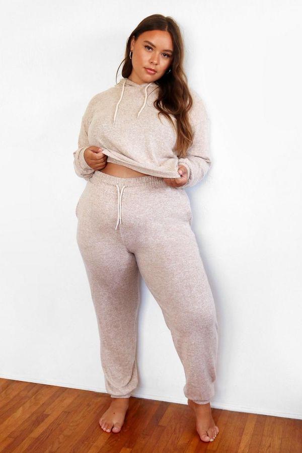 A model wearing a plus-size sweatsuit in pink.