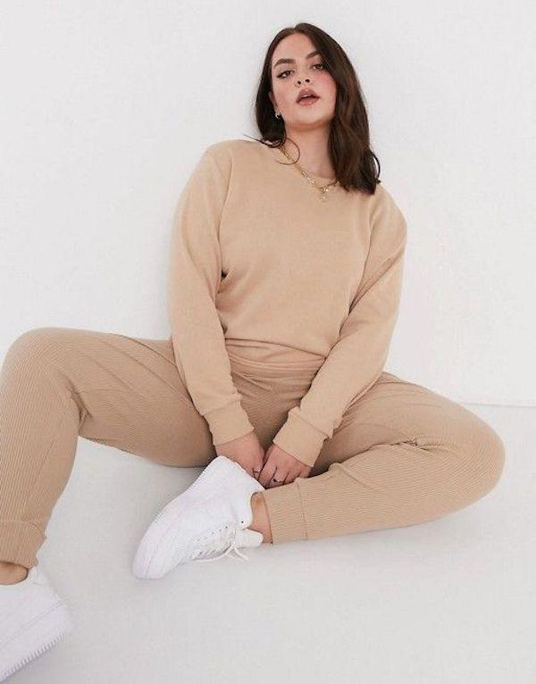 A model wearing a plus-size sweatsuit in tan.