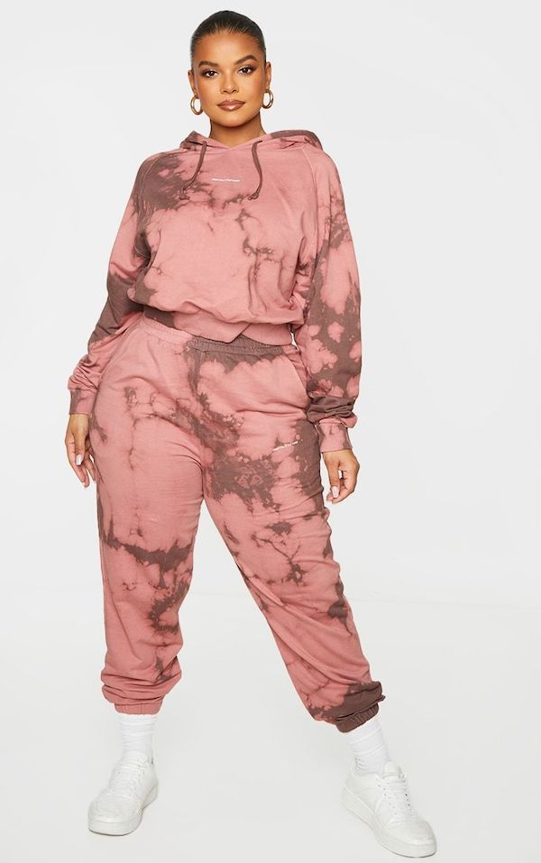 A model wearing a plus-size sweatsuit in brown and pink tie-dye.