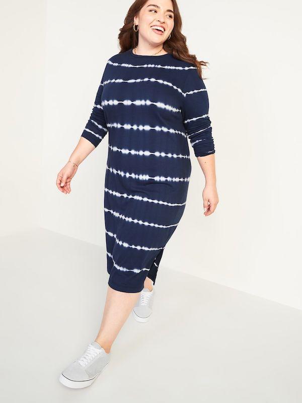 A model wearing a plus-size t-shirt dress in blue and white tie-dye stripe.