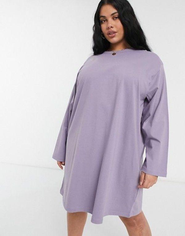 A model wearing a plus-size t-shirt dress in purple.
