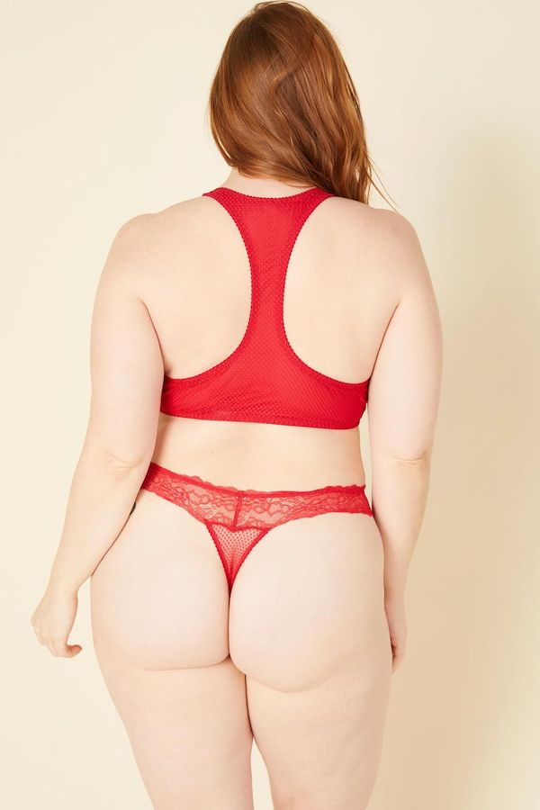 A model wearing a plus-size thong in red.