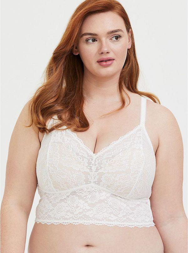 A model wearing a plus-size white bralette.