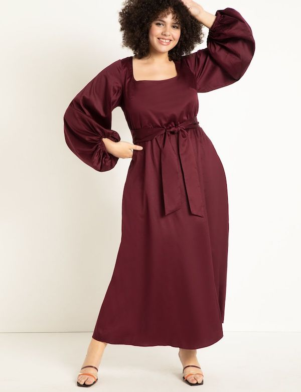 A model wearing a plus-size maxi dress in burgundy.