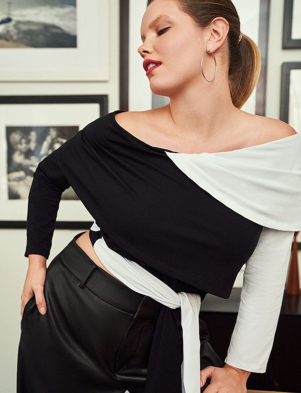 A model wearing a plus-size asymmetric top in black and white.