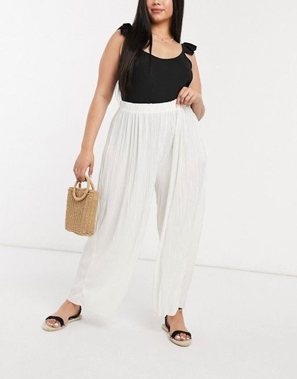 A model wearing plus-size beach pants in white.