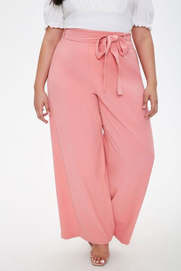 A model wearing plus-size beach pants in pink.