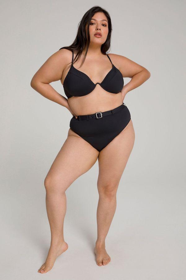 A model wearing a plus-size belted swimsuit in black.