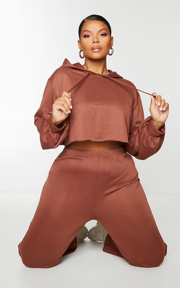 A model wearing a plus-size cropped hoodie in brown.