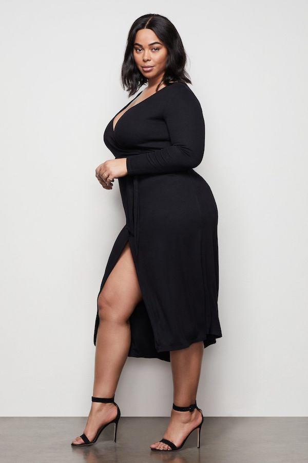 A model wearing a plus-size midi dress in black.