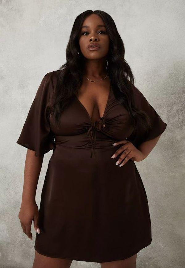 A model wearing a plus-size mini dress in dark brown.