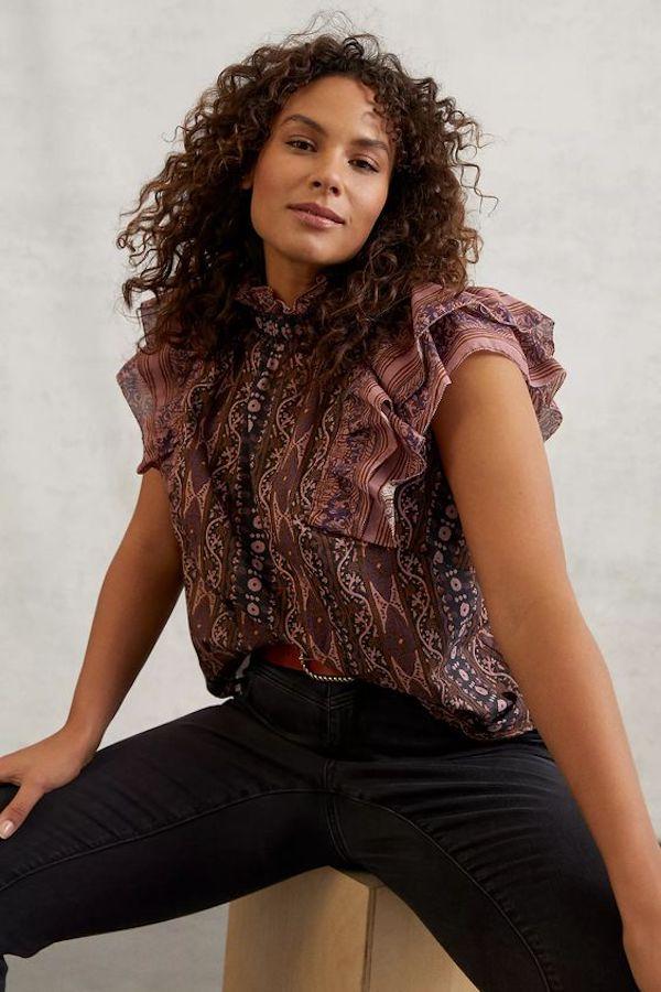 A model wearing a plus-size top in dark purple.